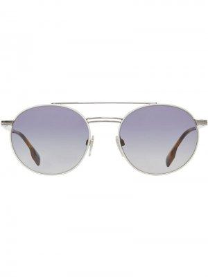 Солнцезащитные очки в круглой оправе с верхней планкой Burberry. Цвет: серебристый