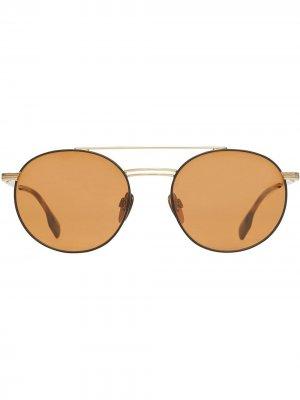 Солнцезащитные очки в круглой оправе с верхней планкой Burberry. Цвет: золотистый